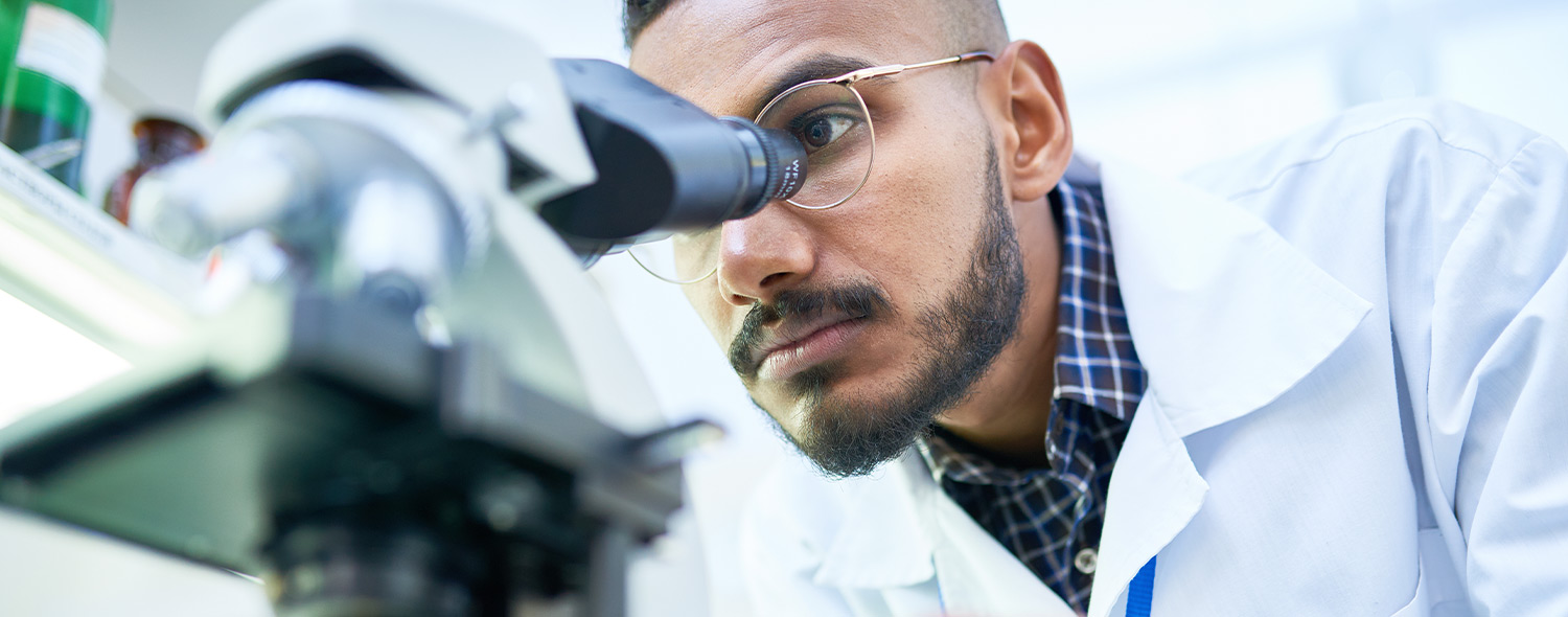 Up close of scientist using microscope